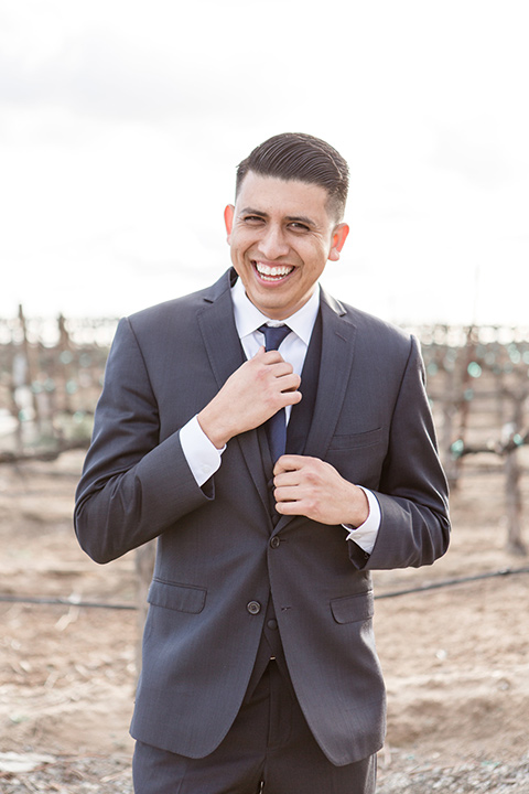 Lorimar-winery-shoot-groom-alone-in-a-navy-suit-with-a-blue-tie