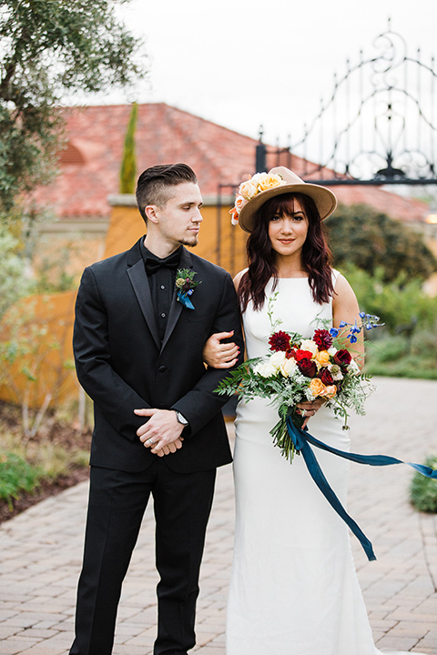 bride and groom standing facing camera bride in a bohemian style dress with a high neckline and lace with a hat groom in an all-black tuxedo look with a black shirt and bow