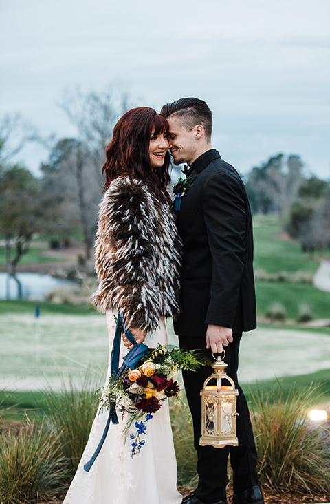 bride in fur holding lantern bride in a bohemian style dress with a high neckline and lace with a hat groom in an all black tuxedo look with a black shirt and bow