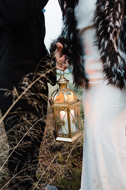 Los Robles Greens Shoot close up on lanterns bride in a bohemian style dress with a high neckline and lace with a hat groom in an all-black tuxedo look with a black shirt and bow