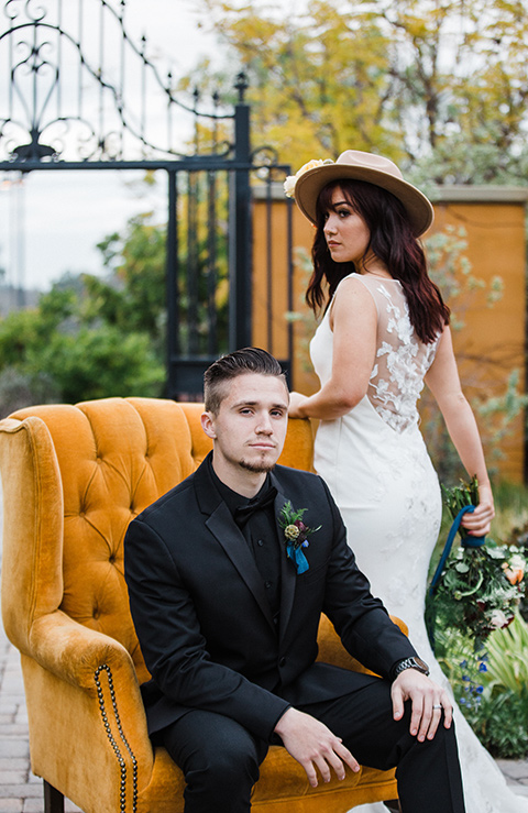 groom sitting bride stands bride in a bohemian style dress with a high neckline and lace with a hat groom in an all black tuxedo look with a black shirt and bow