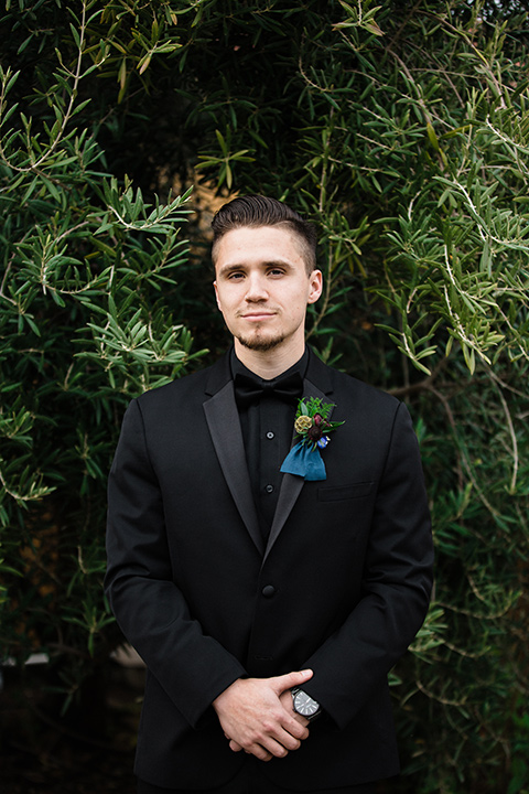 groom standing alone in an all black tuxedo look with a black shirt and bow