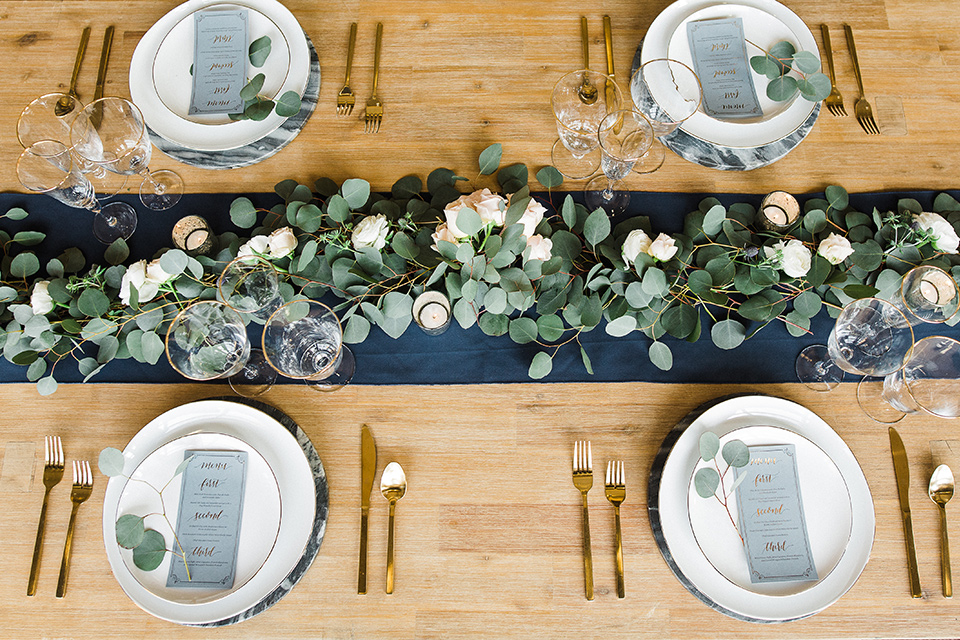 Los Robles Greens Shoot table decor and flatware with white plates and gold flatware on a wooden table with green florals and table runner