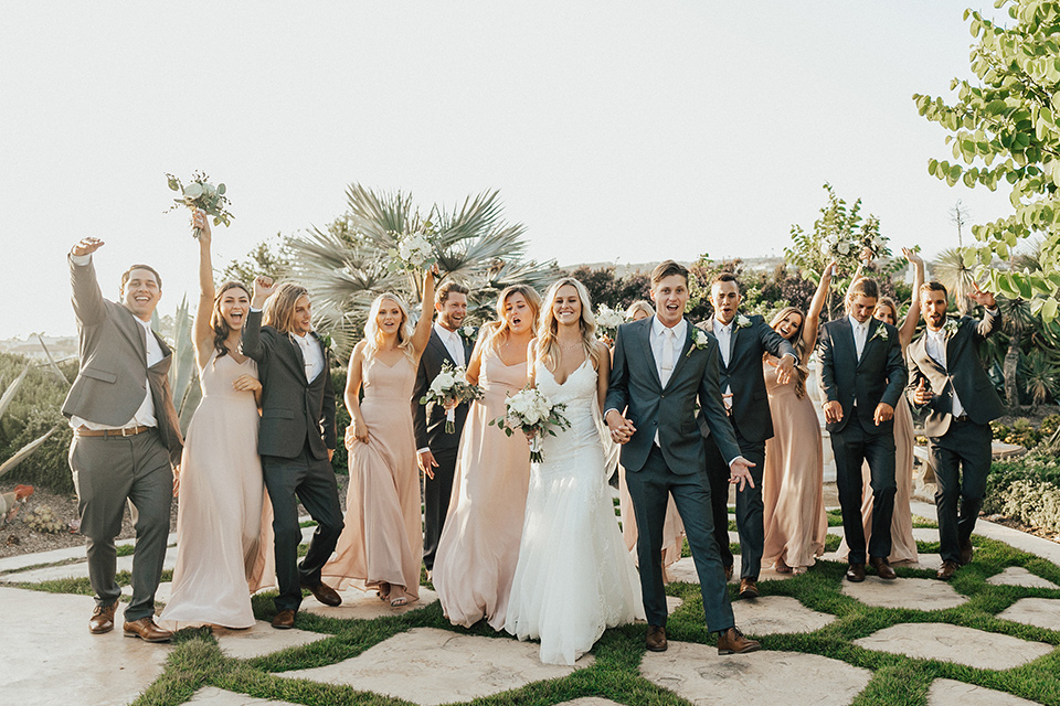 monarch-beach-resort-bridal-party-with-hands-up-beach-resort-black-and-white-photo-close-up-of-bride-and-groom-bride-in-a-lace-dress-with-thin-straps-groom-in-a-grey-suit-with-ivory-long-tie