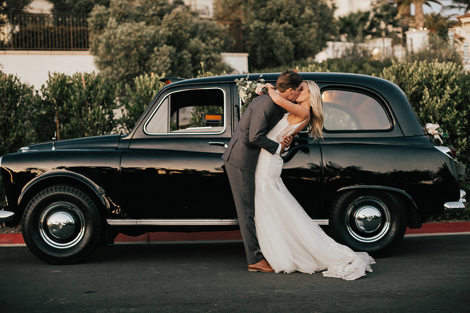 monarch-beach-resort-bride-and-groom-in-front-of-old-car-bride-in-a-lace-dress-with-thin-straps-groom-in-a-grey-suit-with-ivory-long-tie