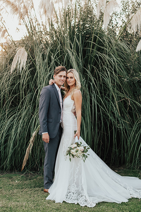 monarch-beach-resort-bride-and-groom-in-front-of-plants-bride-in-a-lace-dress-with-thin-straps-groom-in-a-grey-suit-with-ivory-long-tie