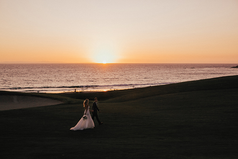 monarch-beach-resort-bride-and-groom-walking-with-sunset-and-ocean-behind-them-in-a-lace-dress-with-thin-straps-groom-in-a-grey-suit-with-ivory-long-tie