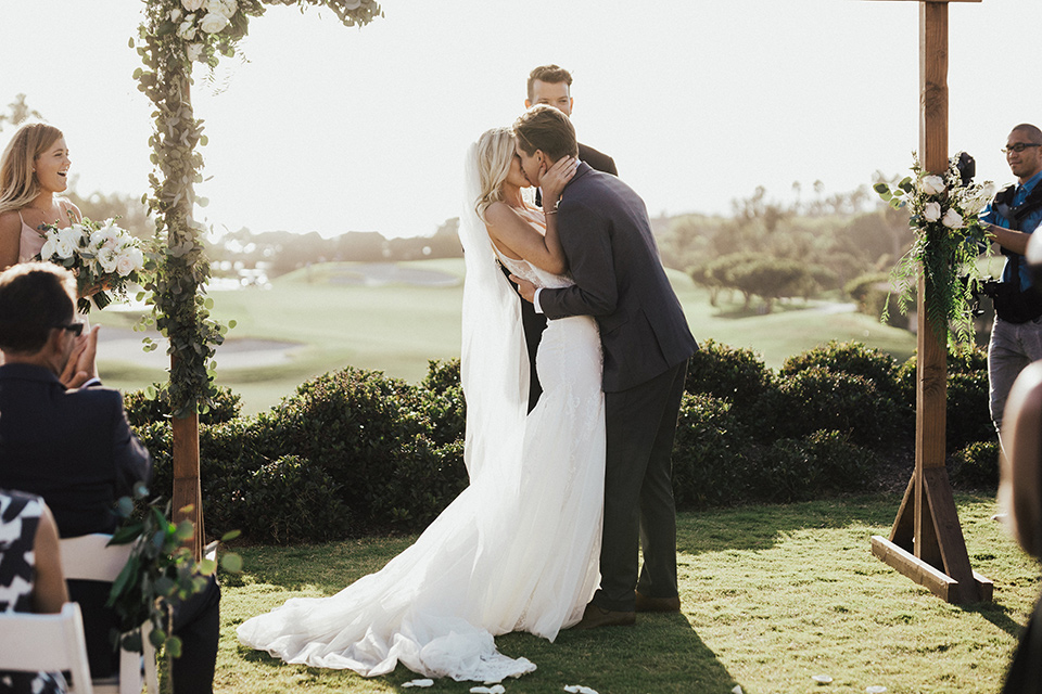 monarch-beach-resort-ceremony-kiss-bride-in-a-lace-dress-with-thin-straps-groom-in-a-grey-suit-with-ivory-long-tie