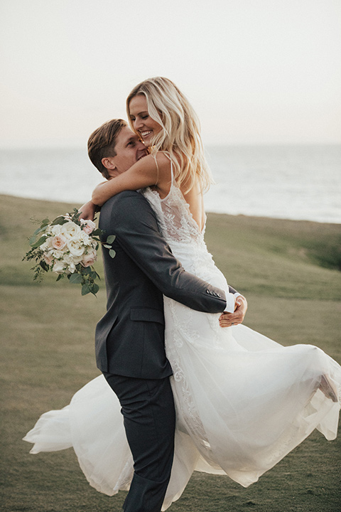 monarch-beach-resort-groom-picking-up-bride-bride-in-a-lace-dress-with-thin-straps-groom-in-a-grey-suit-with-ivory-long-tie