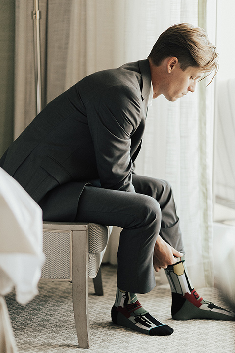 monarch-beach-resort-groom-putting-on-shoe-groom-in-a-grey-suit-with-ivory-long-tie