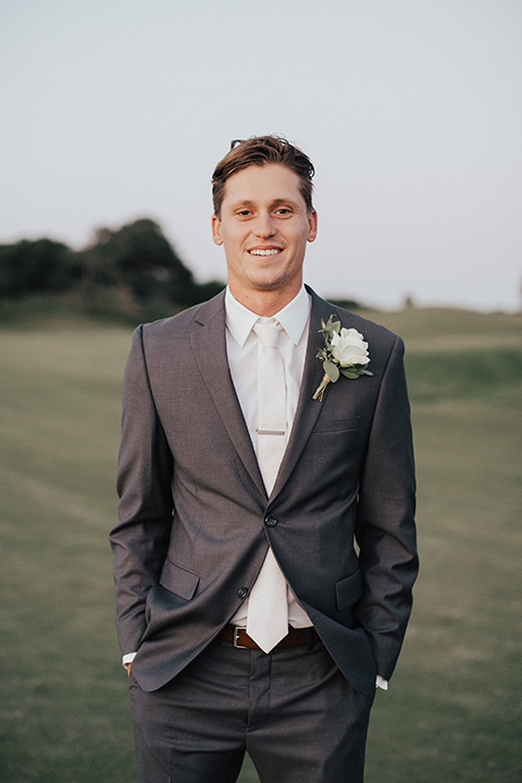 monarch-beach-resort-groom-standing-groom-in-a-grey-suit-with-ivory-long-tie