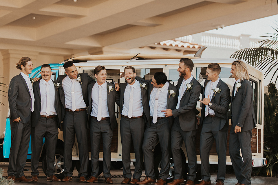 monarch-beach-resort-groomsmen-in-front-of-van-smiling-groom-in-a-grey-suit-with-ivory-long-tie
