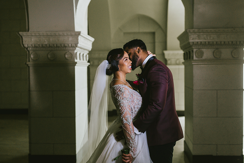 majestic-downtown-los-angeles-shoot-bride-and-groom-close-embrace-bride-in-a-tulle-ballgown-with-a-beaded-bodice-with-long-sleeves-groom-in-a-burgundy-tuxedo-with-a-shawl-lapel-and-black-bow-tie