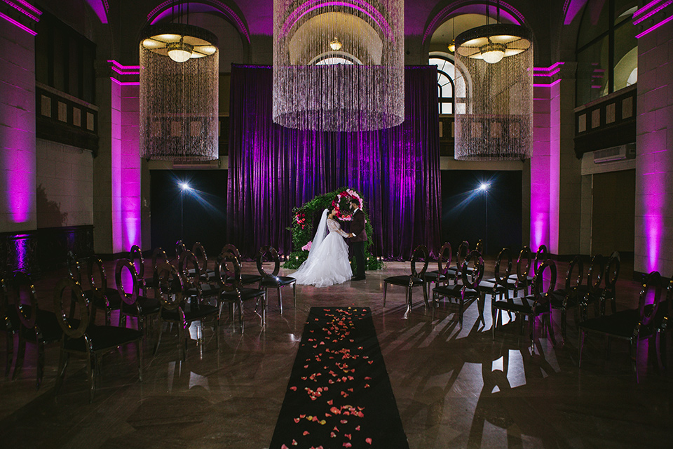 majestic-downtown-los-angeles-shoot-bride-and-groom-at-ceremony-bride-and-groom-close-embrace-bride-in-a-tulle-ballgown-with-a-beaded-bodice-with-long-sleeves-in-a-burgundy-tuxedo-in-a-shawl-lapel-and-black-bow-tie