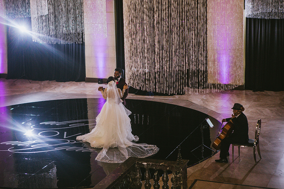 majestic-downtown-los-angeles-shoot-bride-and-groom-dancing-bride-and-groom-close-embrace-bride-in-a-tulle-ballgown-with-a-beaded-bodice-with-long-sleeves-the-groom-in-a-burgundy-shawl-lapel-tuxedo-with-a-black-bow-tie