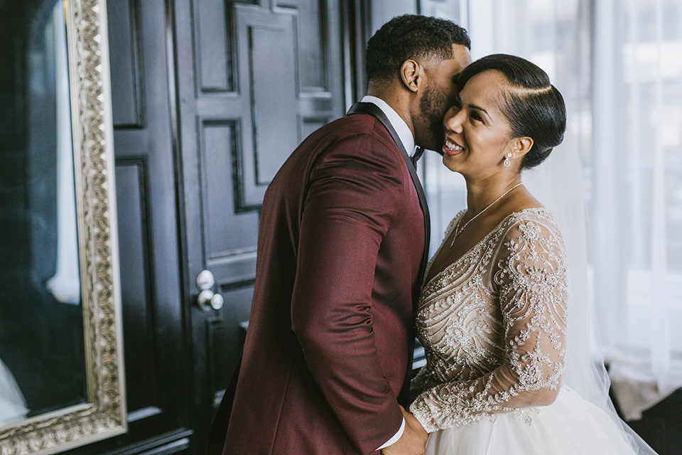 majestic-downtown-los-angeles-shoot-bride-and-groom-smiling-and-laughing-close-bride-and-groom-close-embrace-bride-in-a-tulle-ballgown-with-a-beaded-bodice-with-long-sleeves-groo-in-a-burgundy-tuxedo-with-a-satin-lapel-and-black-bow-tie