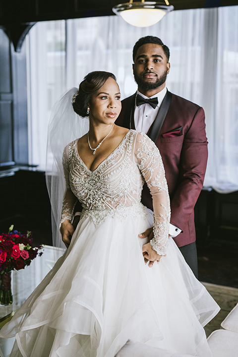 majestic-downtown-los-angeles-shoot-bride-and-groom-standing-groom-behind-bride-bride-in-a-tulle-ballgown-with-a-beaded-bodice-with-long-sleeves-and-the-groom-in-a-burgundy-tuxedo-with-a-black-satin-lapel-and-black-bow-tie