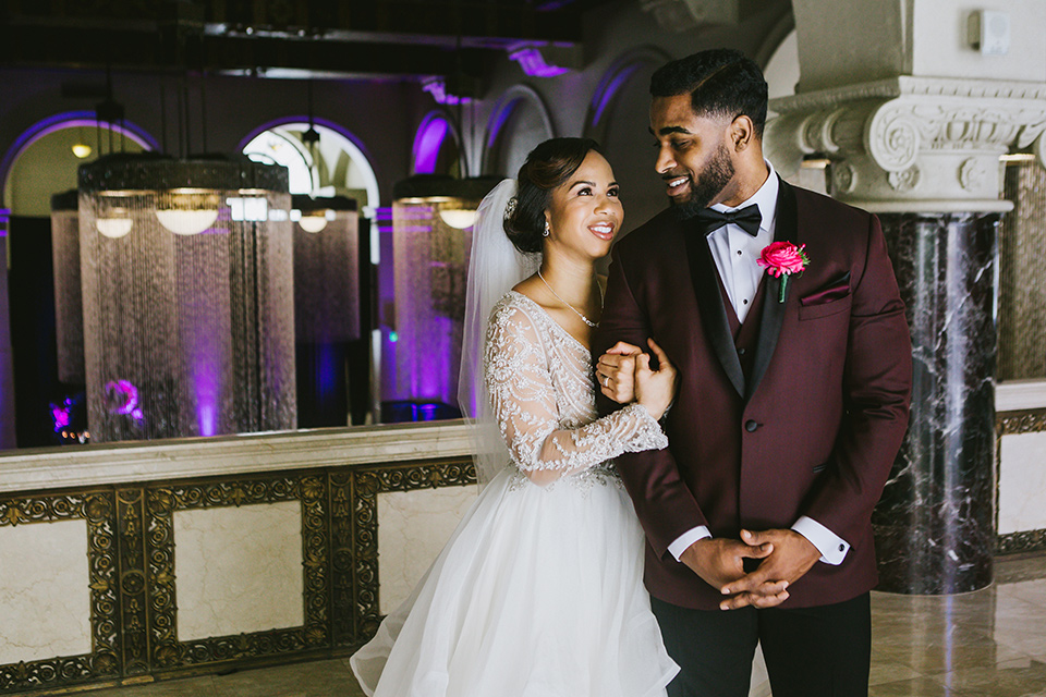 majestic-downtown-los-angeles-shoot-bride-behind-groom-groom-smiling-at-bride-bride-and-groom-close-embrace-bride-in-a-tulle-ballgown-with-a-beaded-bodice-with-long-sleeves-groo-in-a-burgundy-tuxedo-with-a-satin-lapel-and-black-bow-tie