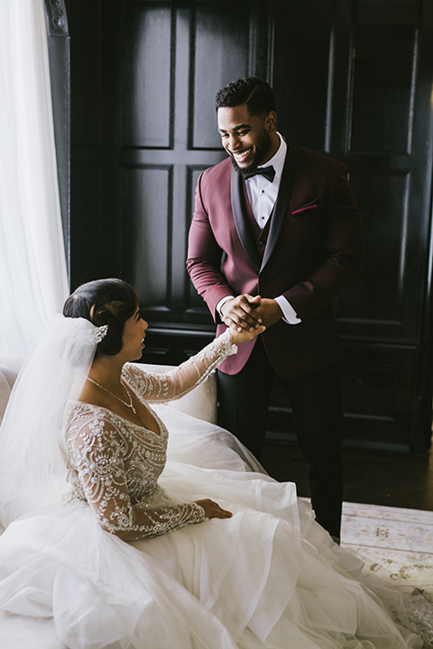 majestic-downtown-los-angeles-shoot-bride-sitting-groom-standing-looking-at-her-the-bride-in-a-tulle-ball-gown-with-beaded-bodice-and-long-sleeves-the-groom-in-a-burgundy-tuxedo-with-a-black-shawl-lapel-and-black-bow-tie