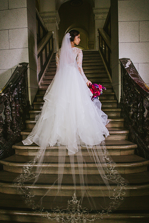 majestic-downtown-los-angeles-shoot-bride-standing-on-steps-in-a-tulle-ballgown-with-a-beaded-bodice-with-long-sleeves
