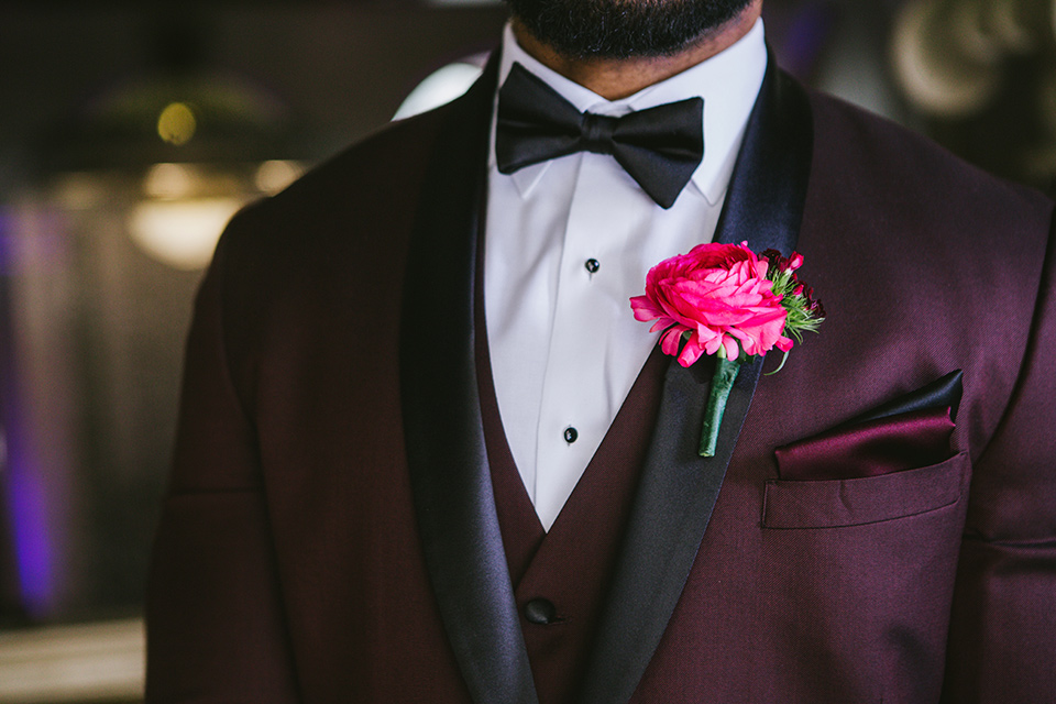 majestic-downtown-los-angeles-shoot-groom-attire-close-up-in-a-burgundy-tuxedo-with-a-satin-lapel-and-black-bow-tie