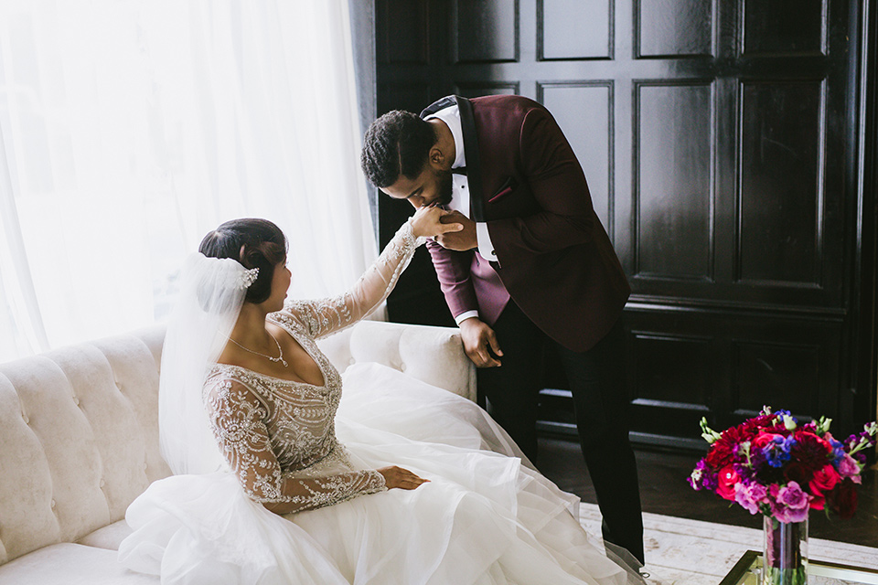 majestic-downtown-los-angeles-shoot-groom-kissing-brides-hand-bride-in-a-tulle-ballgown-with-a-beaded-bodice-with-long-sleeves-groo-in-a-burgundy-tuxedo-with-a-satin-lapel-and-black-bow-tie