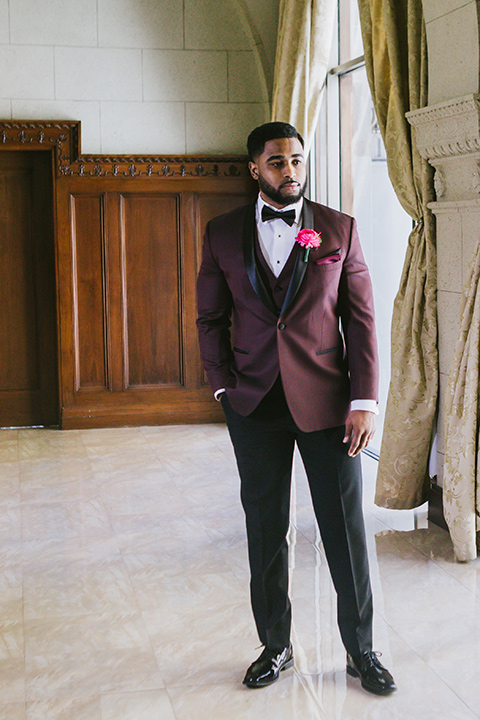 majestic-downtown-los-angeles-shoot-groom-standing-alone-in-a-burgundy-tuxedo-with-a-black-shawl-lapel-and-black-bow-tie