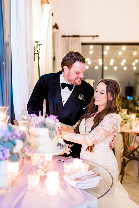 bride in a white lace gown with long sleeves and a tulle skirt and the groom in a black velvet tuxedo with a black bow tie cutting a cake