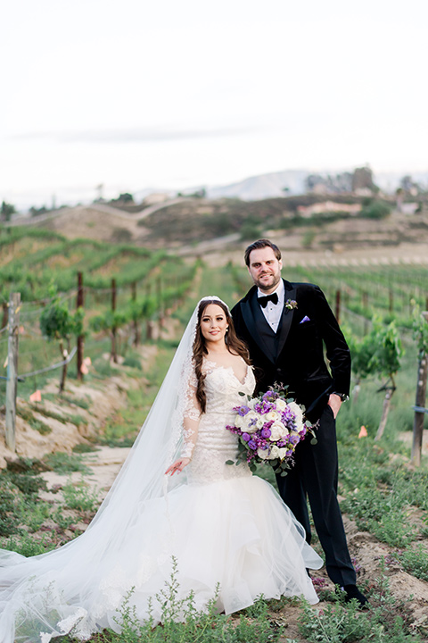 bride in a white lace gown with long sleeves and a tulle skirt and the groom in a black velvet tuxedo with a black bow tie