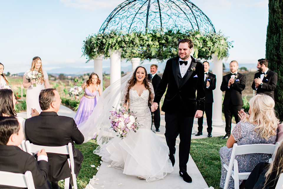 bride in a white lace gown with long sleeves and a tulle skirt and the groom in a black velvet tuxedo with a black bow tie, the bridesmaids in purple gowns and the groomsmen in black tuxedos