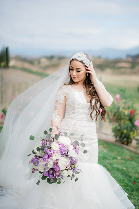 bride in a white lace gown with long sleeves and a tulle skirt