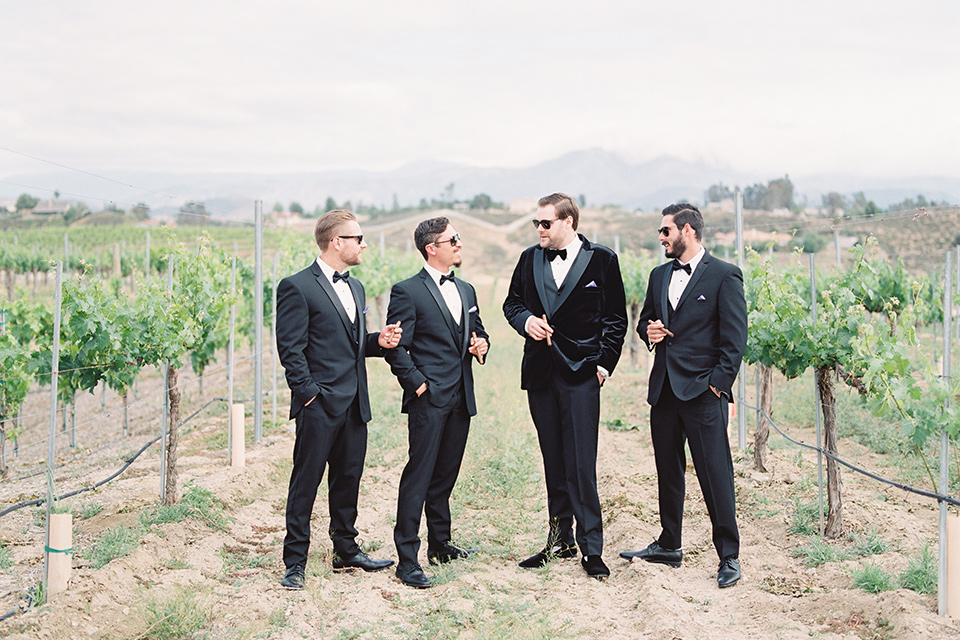 the groom in a black velvet tuxedo with a black bow tie, the and the groomsmen in black tuxedos