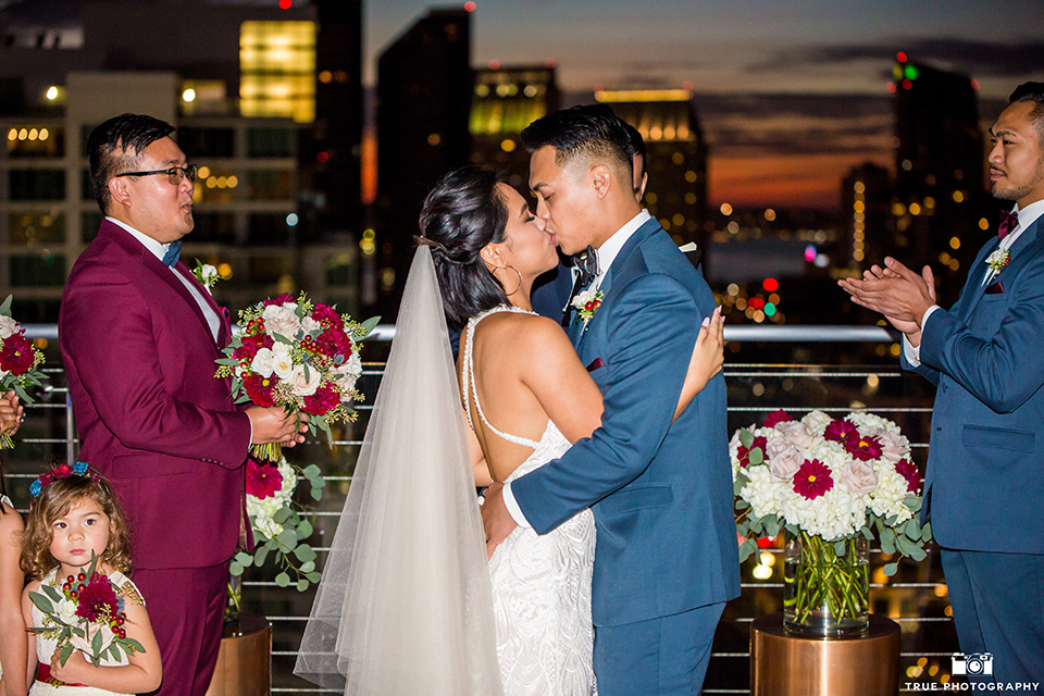 skybox-real-wedding-bride-and-groom-first-kiss-bride-wearing-a-fitting-lace-dress-with=straps-groom-wearing-a-blue-suit-bridesmaids-in-burgundy-groomsmen-in-blue
