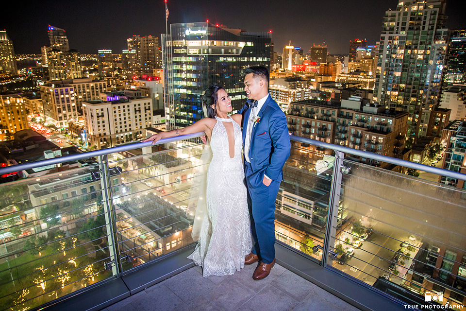 skybox-real-wedding-bride-and-groom-with-lighted-up-city-behind-them-bride-wearing-a-fitting-lace-dress-with=straps-groom-wearing-a-blue-suit-bridesmaids-in-burgundy-groomsmen-in-blue