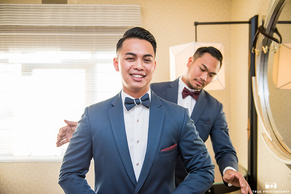 skybox-real-wedding-groom-getting-ready-bride-wearing-a-fitting-lace-dress-with=straps-groom-wearing-a-blue-suit-bridesmaids-in-burgundy-groomsmen-in-blue