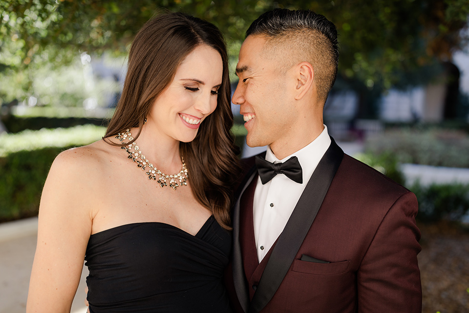 Maternity-workshop-close-up-on-mom-and-dad-mom-wearing-a-chic-black-formfittng-gown-dad-wearing-a-burgundy-tuxedo-and-black-bow-tie