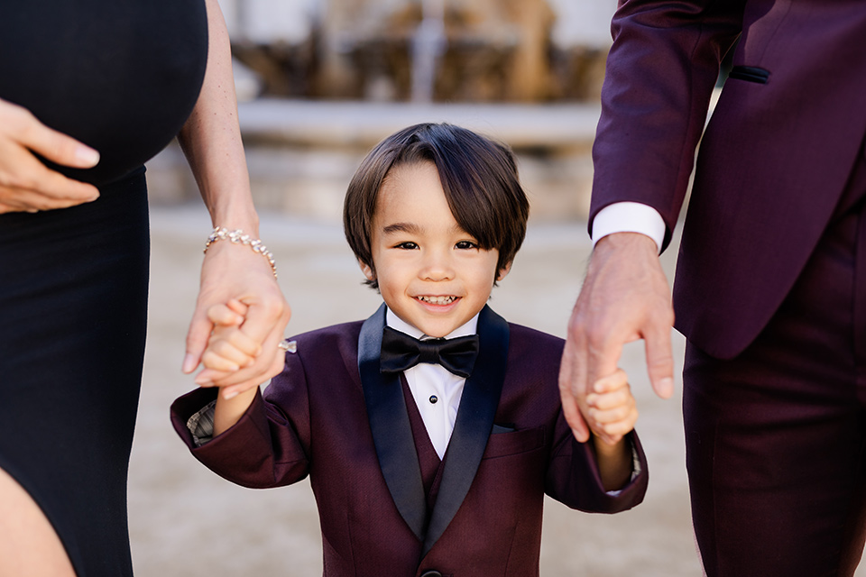 Maternity-workshop-close-up-on-little-boy-mom-wearing-a-chic-black-formfittng-gown-dad-wearing-a-burgundy-tuxedo-and-black-bow-tie-little-boy-wearing-a-burgundy-tux-that-matches-his-father