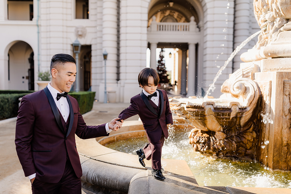 Maternity-workshop-father-and-son-walking-dad-wearing-a-burgundy-tuxedo-and-black-bow-tie-little-boy-wearing-a-burgundy-tux-that-matches-his-father