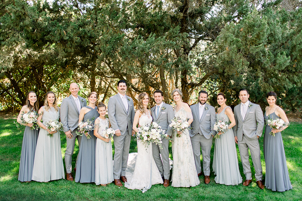 Temecula-Creek-Inn-Wedding-bridal-party-bridesmaids-in-various-dusty-blue-dresses-groomsmen-in-light-grey-suits-with-blue-suits-bride-in-a-form-fitting-lace-gown-with-an-illusion-back-detail-groom-in-a-light-grey-suit-with-a-light-blue-polka-dot-tie