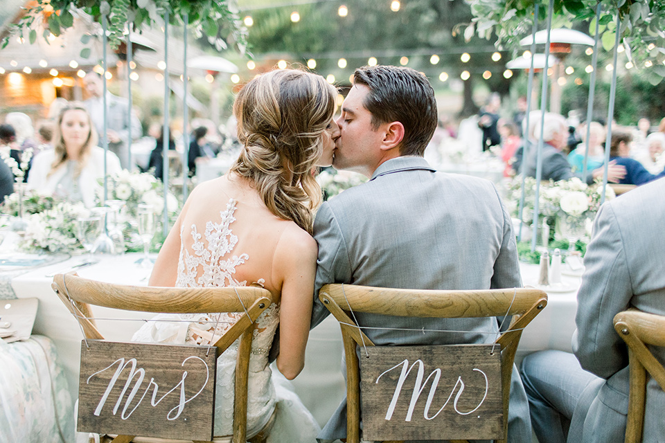 Temecula-Creek-Inn-Wedding-bride-and-groom-kissing-at-sweetheart-table-bride-in-a-form-fitting-lace-gown-with-an-illusion-back-detail-groom-in-a-light-grey-suit-with-a-light-blue-polka-dot-tie