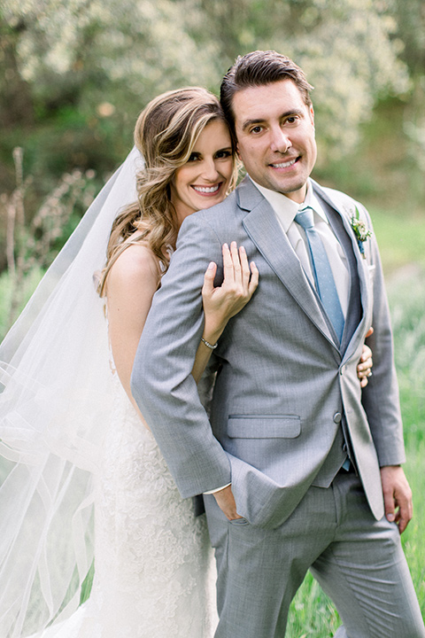 Temecula-Creek-Inn-Wedding-bride-and-groom-looking-at-camera-bride-in-a-forfitting-lace-gown-with-an-illusion-back-detai-groom-in-a-light-grey-suit-with-light-blue-polka-dot-tiel