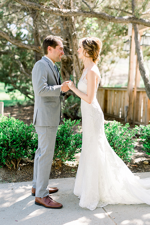 Temecula-Creek-Inn-Wedding-bride-and-groom-looking-at-each-other-bride-in-a-lace-dress-with-an-illusion-back-groom-in-a-light-grey-suit-with-blue-patterned-tie