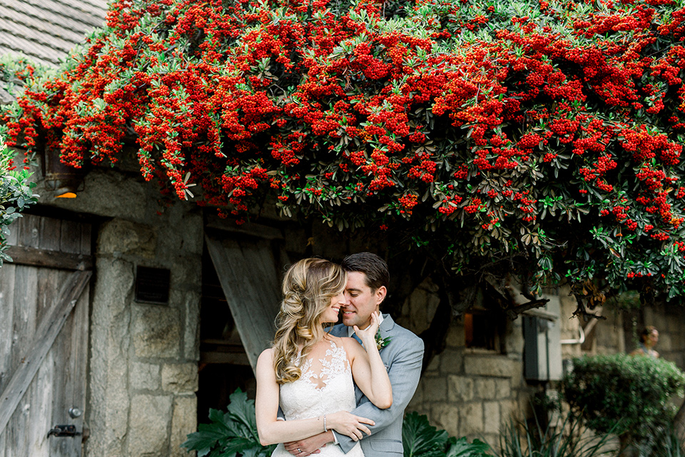 Temecula-Creek-Inn-Wedding-bride-and-groom-under-bougainvillea-bride-in-a-form-fitting-lace-gown-with-an-illusion-back-detail-groom-in-a-light-grey-suit-with-a-light-blue-polka-dot-tie