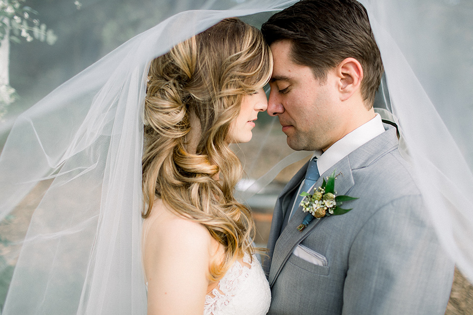 Temecula-Creek-Inn-Wedding-bride-and-groom-under-veil-bride-in-a-form-fitting-lace-gown-with-an-illusion-back-detail-groom-in-a-light-grey-suit-with-a-light-blue-polka-dot-tie