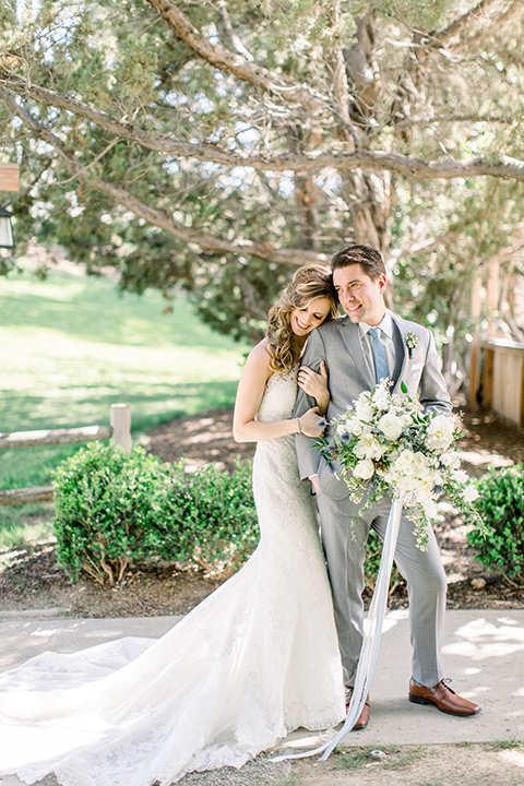 Temecula-Creek-Inn-Wedding-bride-resting-head-on-groom-groom-holding-flowers-bride-in-a-lace-dress-with-an-illusion-back-groom-in-a-light-grey-suit-with-blue-patterned-tie