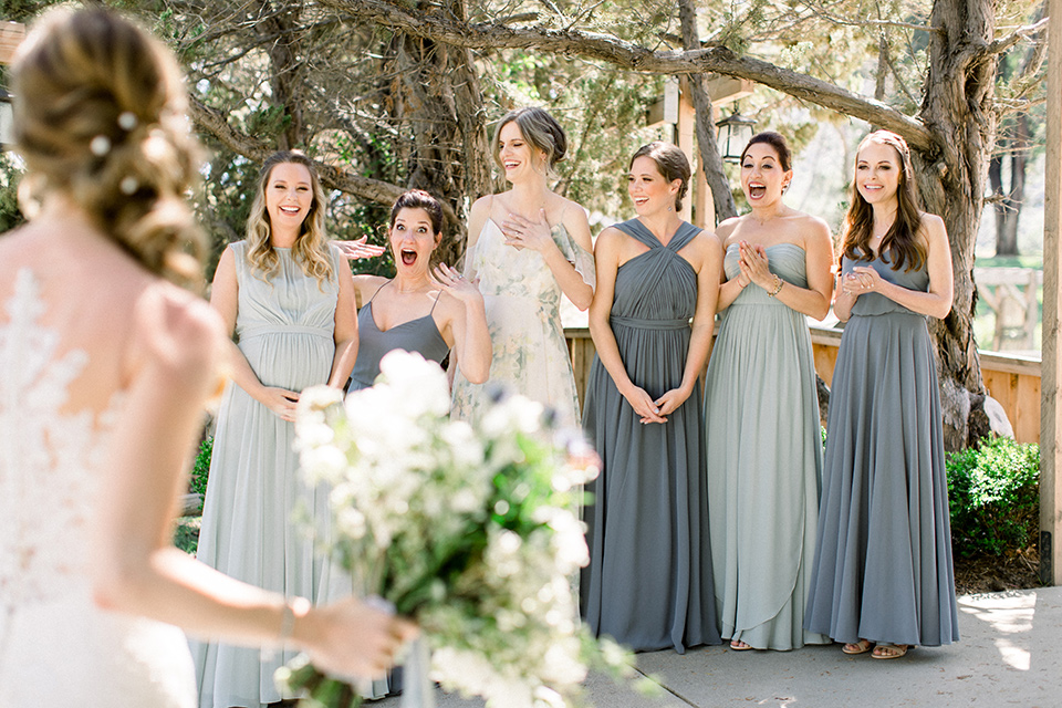 Temecula-Creek-Inn-Wedding-bridesmaids-see-bride-for-the-first-time-bride-in-a-form-fitting-lace-gown-with-an-illusion-back-detail-bridesmaids-in-different-shades-of-dusty-blue-dresses