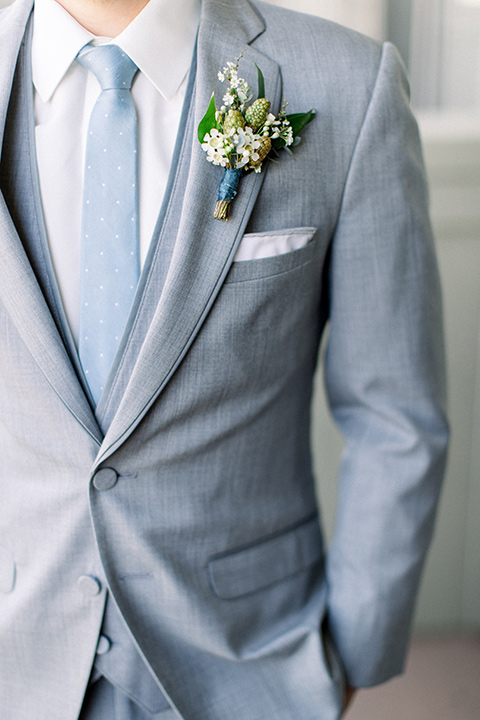 Temecula-Creek-Inn-Wedding-close-up-on-groom-attire-in-a-light-grey-suit-with-light-blue-polka-dot-tie