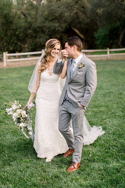 Temecula-Creek-Inn-Wedding-groom-kissing-brides-hand-bride-in-a-forfitting-lace-gown-with-an-illusion-back-detai-groom-in-a-light-grey-suit-with-light-blue-polka-dot-tiel