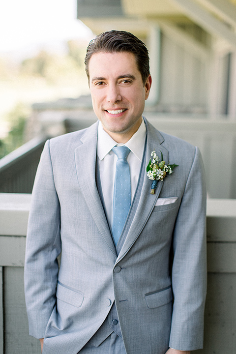 Temecula-Creek-Inn-Wedding-groom-smiling-at-camera-in-a-light-grey-suits-with-light-blue-ties