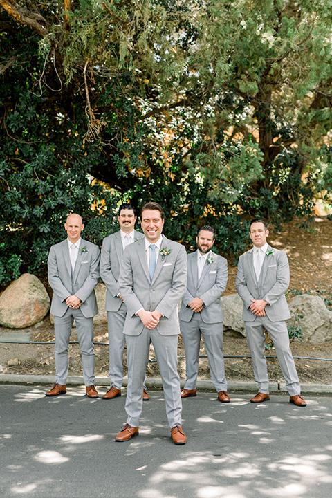 Temecula-Creek-Inn-Wedding-groom-standing-in-front-og-groomsmen-andgroom-in-light-grey-suits-with-light-blue-ties
